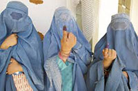 Afghan women in blue burkas show their fingers