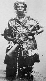 A black woman in military clothes holding a gun