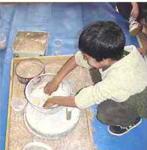 a brown-skinned boy with black hair with his hands in a mixing bowl