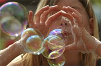 a white child blows soap bubbles