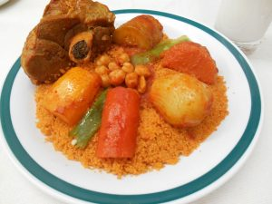 Reddish couscous on a plate with vegetables and lamb