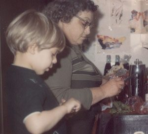 older white woman and young white boy peeling vegetables together at the kitchen sink