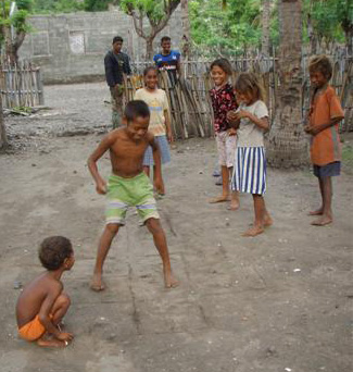 brown-skinned boys and girls play hopscotch on a board scratched into bare dirt