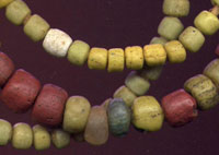 Three strands of beads with yellow, white, and red beads
