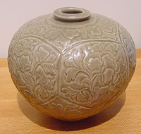 brown pottery vase with incised or molded decoration