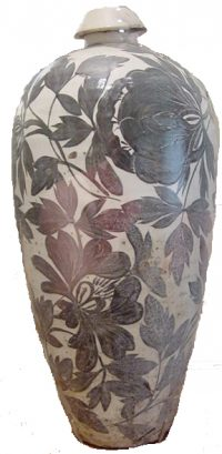 white vase with brown leaf decoration on it