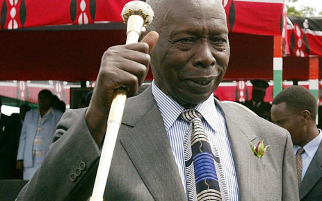 An older black man in a suit holding an African staff