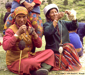 brightly dressed brown women sitting on the ground spinning with hand spindles