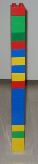 a tower built from legos in a pattern of blue,red, and yellow