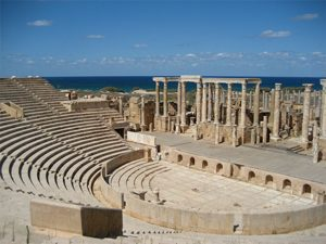 A stone theater and stage buildings looking out to sea
