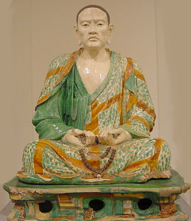 clay statue of an asian man sitting cross-legged wearing brown and green robes
