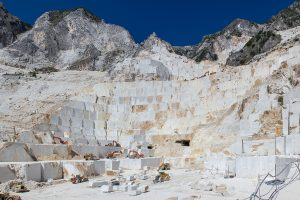 A bright white cliff cut in rectangular shapes, with a blue sky behind it - what is marble?