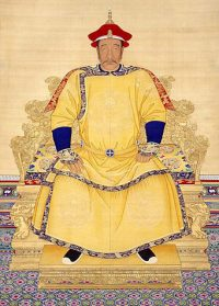An Asian man sitting on a big chair wearing yellow robes