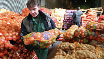 A man carrying a brightly colored sack of potatoes with other potatoes in the background