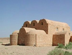 A stone building in the desert with three barrel vaults