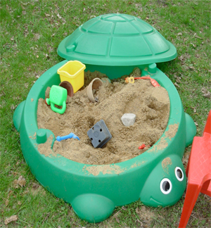 a green turtle sandbox with toys and sand (and roundworms?) in it