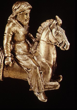 gold carving of a man riding a horse wearing pants and a short tunic with long sleeves