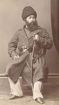 A Central Asian man with a thick black beard and a heavy coat