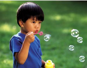 a boy blowing soap bubbles