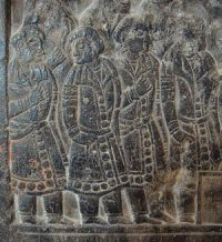 stone carving of Sogdian traders wearing fancy belted robes