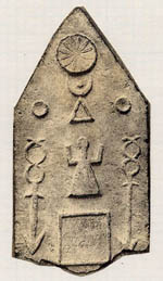 A tombstone with a rough image of a woman with her arms raised up and various moon and triangle symbols - Early African religion