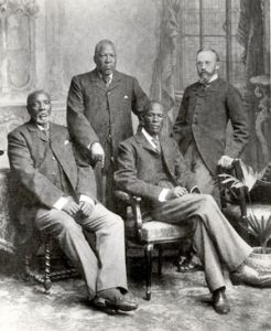 three older, serious black men sitting in chairs wearing european-style suits; a white man standing behind them