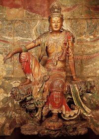 a statue of Guanyin sitting with one knee up and her arm on her knee