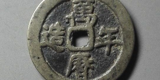 circular coin with four chinese characters on it and a square hole in the center