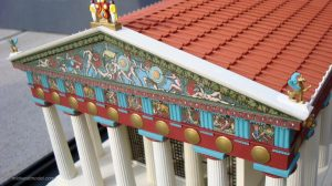 A greek temple painted in red and blue and gold. The columns are left white.