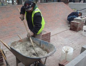 A man mixing concrete in a wheelbarrow