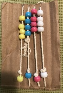 a piece of brown cardboard with four white strings across it, each with four beads, then a knot, and then another bead