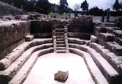 Three levels of stone benches in a U shape around a block in the middle. There's an access stairway at the back of the room. Ruins are in the background. Eratosthenes of Cyrene might have studied here.