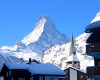 Alps: a village with a tall mountain peak and snow behind it