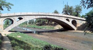 A beautiful curved bridge over a river, in white stone