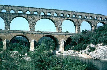 A roman aqueduct - stone arches across a river valley