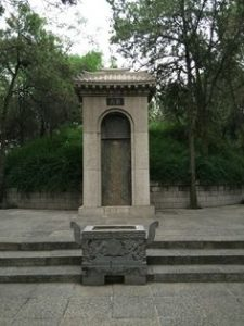 A stone niche and stone steps in a garden: The tomb of Bai Juyi