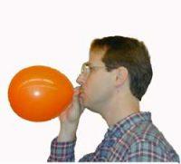 a white man blows up a balloon