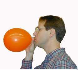 a white man blows up a balloon