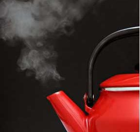 a red tea kettle with white steam coming out of the spout
