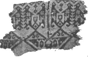 Black and white photo of complicated dark pattern on light scrap of cloth: history of knitting