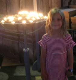 A little girl standing in front of a group of candles
