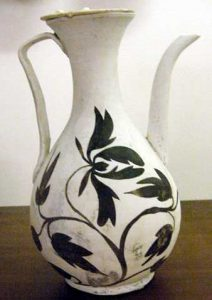 tall white pitcher with black flowers painted on the body