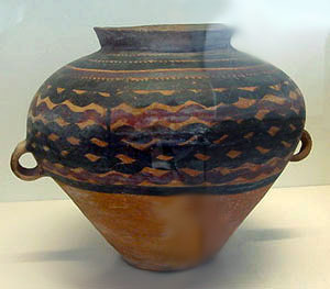 big jar with wavy black lines painted on it horizonatally