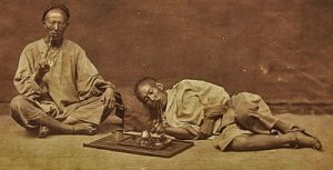 old photo of two men in white tunics lying down smoking opium: the Opium Wars