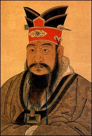 Head and shoulders of a Chinese man with a fancy red and black hat and a very long black mustache: Confucius