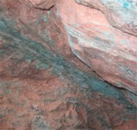 A sheet of reddish rock with green veins running through it