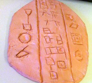 Red clay tablet with signs carved into it.