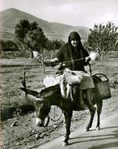 Greek woman spinning while riding a donkey