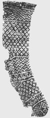 Black and white photo of knitted sock with complicated variety of patterns