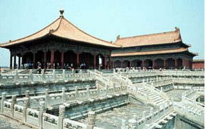 Chinese buildings with swooping roofs and a complicated set of stairs and balconies in front of them